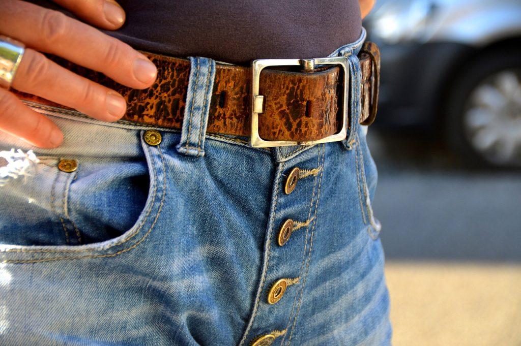 Cintura in pelle marrone su jeans